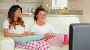 stock-footage-women-sitting-on-the-couch-in-front-of-the-tv
